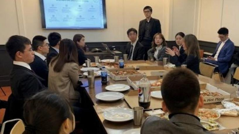 Students sitting around a table listening to a representative from  MSQ Ventures headquarters talk about their company